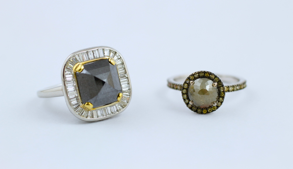 (left to right) A platinum ring featuring a large black diamond and a gold ring with green diamond melee surrounding an opaque green diamond.