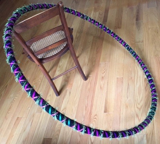"Lisa Gwisdalla.  ""Artful Rotations,"" dance/exercise hoop w/ black hand-crocheted yaarn sleeve laced w/ colored ribbons & eyelash twine, 48"" diam. Follow this artist on  www.Facebook.com  at ""Lisa Gwisdalla"".   FMV   $40       I     GUAR PUR   $50       I     MIN BID$20       I     BID INC$5"