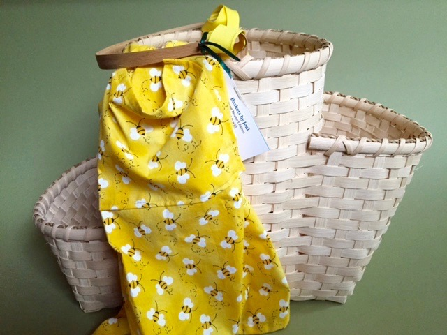 "Weaver's Complaint ""Basket of Pockets,"" hand-woven by Joanne Neubert Raines, 13""H x 21""W; with yellow apron hand-crafted by Maggi Rhudy. Gift of MountainTop Realty:  www.mountaintoprealty.com    FMV   $95      I    GUAR PUR   $119      I    MIN BID$40      I    BID INC$5"