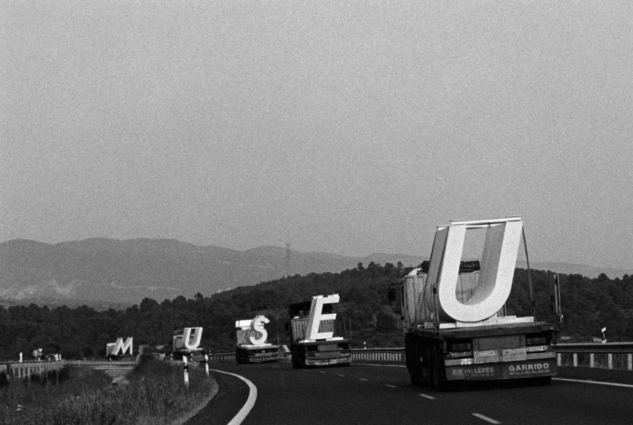 "subtilitas :      Trucks carrying  the large, precast concrete letters of  Mansilla+Tuñón 's   Fine Arts museum  of Castellón in order of  their display  in 1999. Previously,  today .      ""As  they moved through the landscape and the towns, the five letters formed  a word. The emergence of a word, an intruder, implies a culturization  of landscape through thought. A culturization in motion that leaves no  lasting mark. An ephemeral action, limited to four hundred and forty  kilometres and ten hours of travel."""