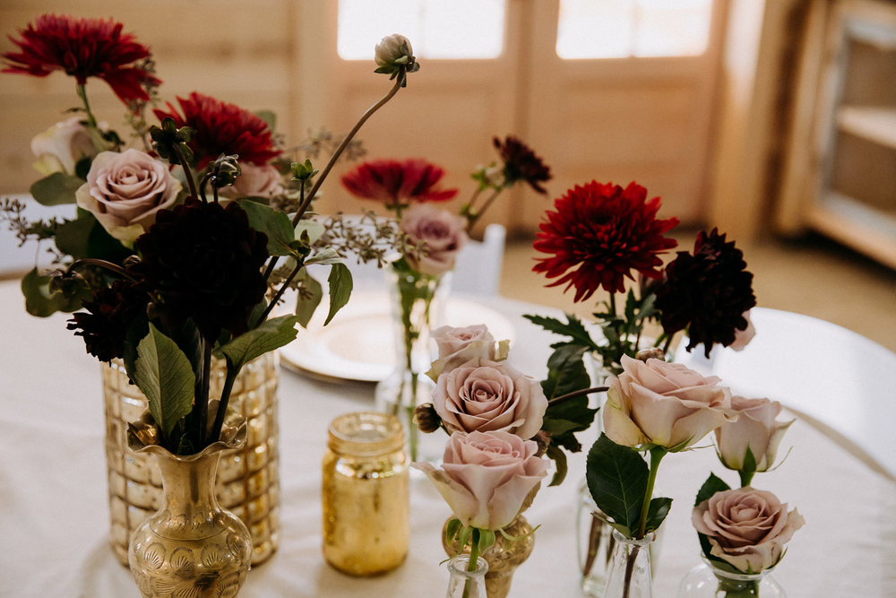 Gold vases, red flowers, and lavender roses