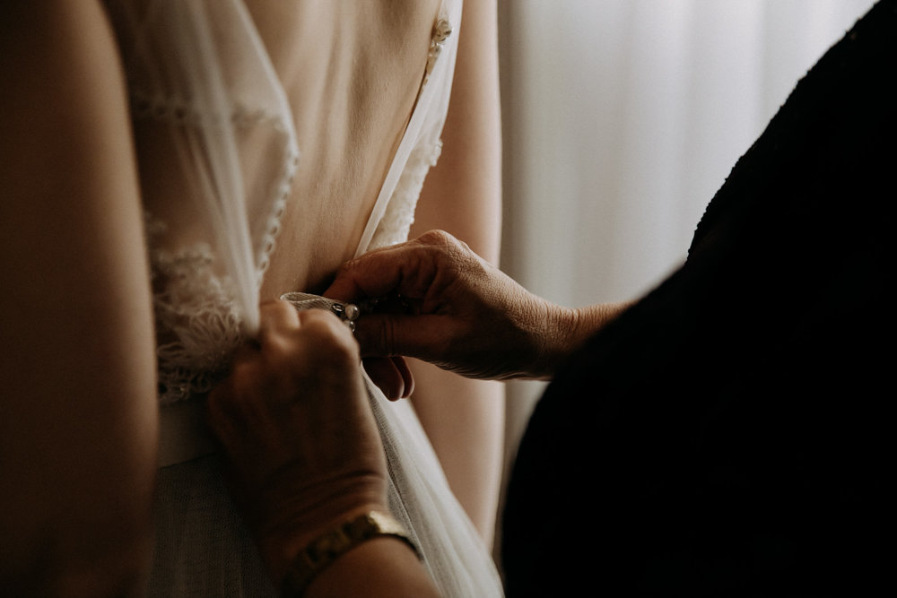 Award-winning image of the mother-of-the-bride buttoning the bride's Watters dress