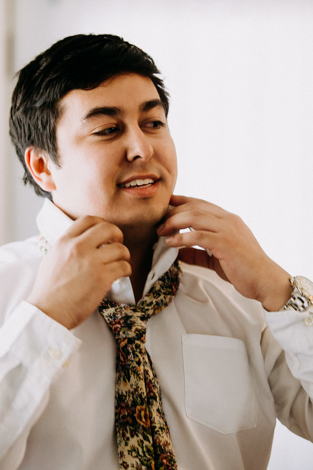 Groom putting on floral tie