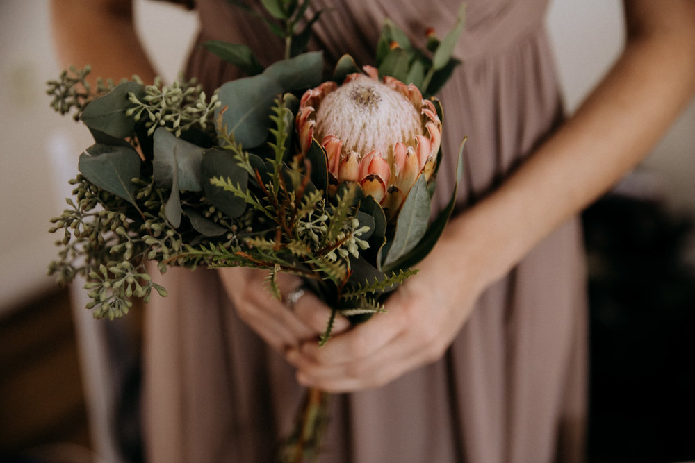 Bridesmaid holding a protea