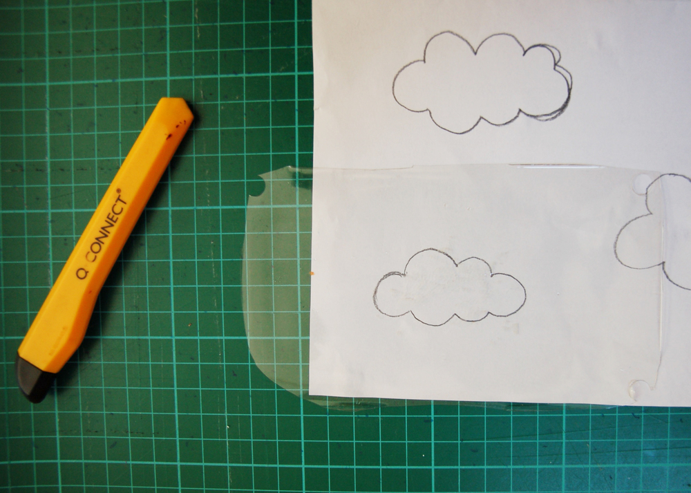 Draw out a cloud shape on paper then place a piece of acetate (or old food packaging!) over the top and cut out the stencil using a craft knife.