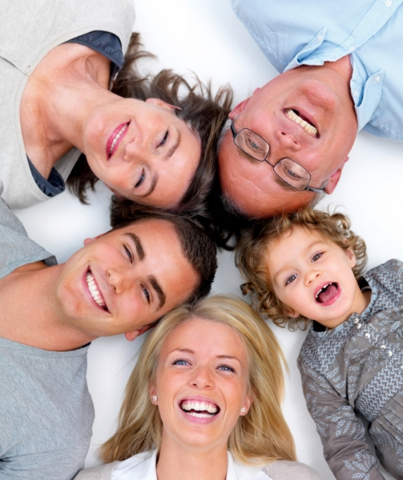 Closeup portrait of a happy family lying in a circle on white floor