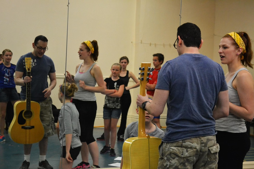 Director Joel Froomkin works with Lauren Lukacek (Maria) and the von Trapp children.