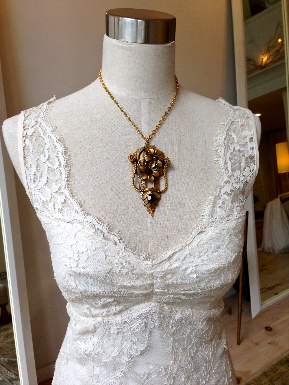 The ruched bodice and sweetheart neckline are both flirty and incredibly flattering! Paired here with a gold and amethyst vintage necklace that evokes the floral pattern found throughout the lace.