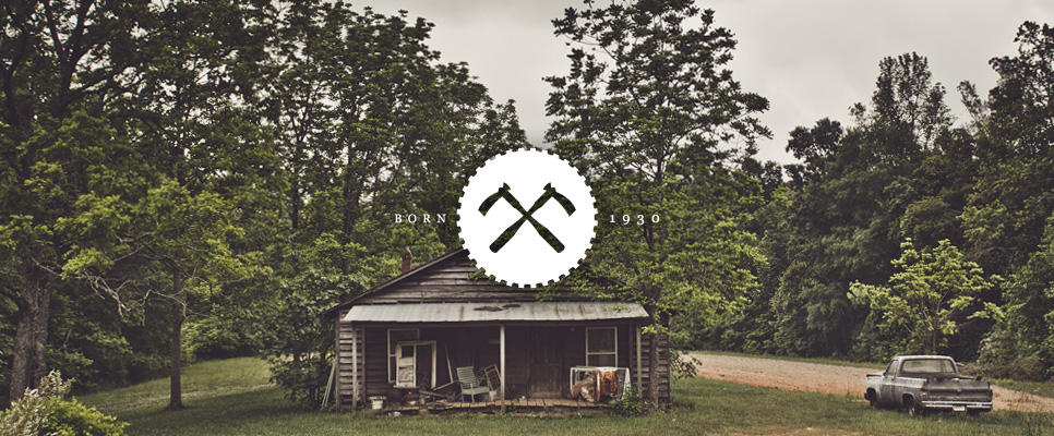 Lamon Luther double axe crossed x icon graphic design with Born 1930 stamp on top of a photograph of an old shed and truck in a wooded clearing.
