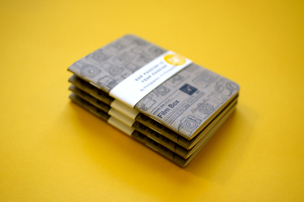 Stack of custom kraft paper notebooks printed by Scout Books for field notes for photographers.