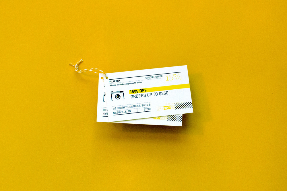 15% off orders over $350 coupon card design. Elements of the graphics are inspired by kodak and polaroid film canisters. Tied together in the corner with yellow and white baker's twine.