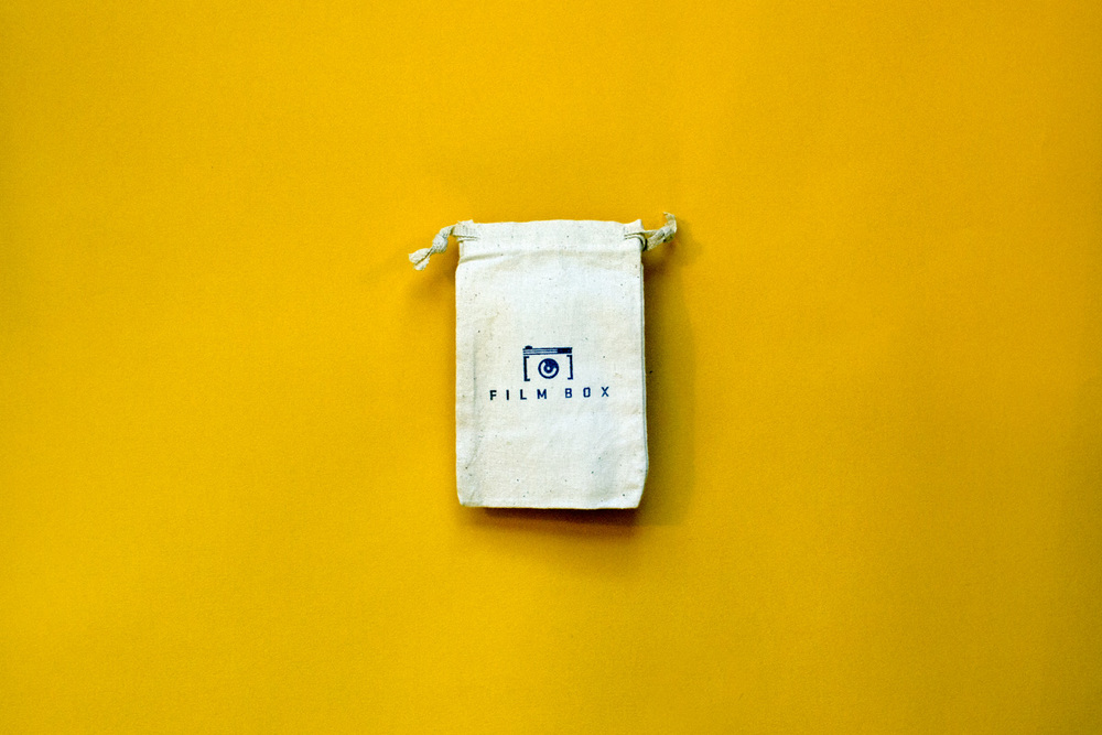 Small drawstring cotton linen bag for film canisters, a giveaway for Film Box, with hand stamped logo on the front.