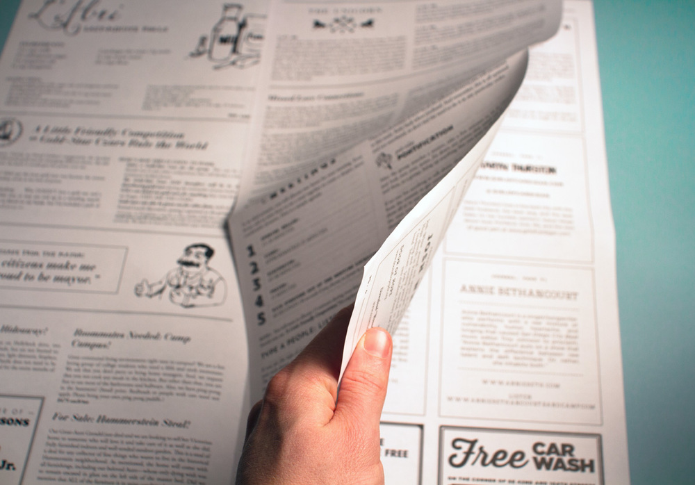 Fake advertisements and news stories are sprinkled in with instructions on how to use the group discussion box set inside the Illumination Project newspaper brochure.