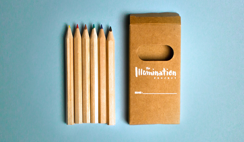 The Illumination Project pencil case, with a custom white logo design on kraft paper box of miniature colored pencils.