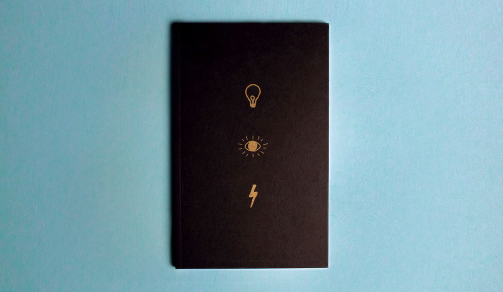 The Illumination Project cover design of the notebook with a pen and ink simple illustration of a lightbulb, eye, and lightning bolt on a black paper cover printed in metallic gold pantone ink.