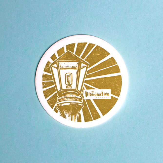 Round coasters with The Illumination Project woodcut illustrations block printed in metallic gold pantone ink features an illustration of a lamp post and the custom logo design.