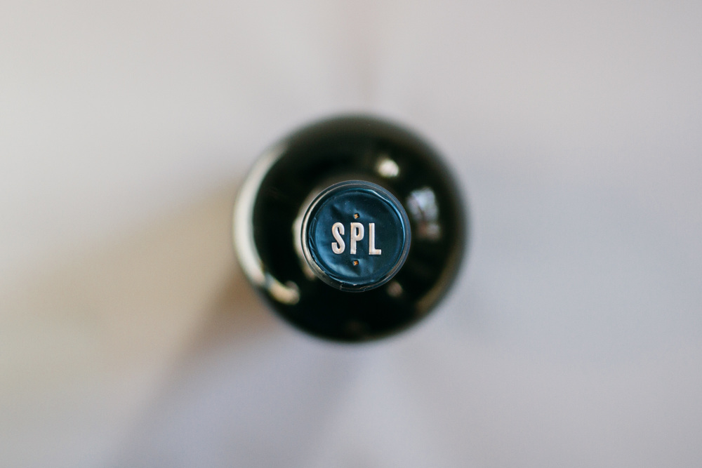 Top of the wine capsule and bottle packaging shows the branding design of the custom SPL letters in silver embossed on a navy wrapper.
