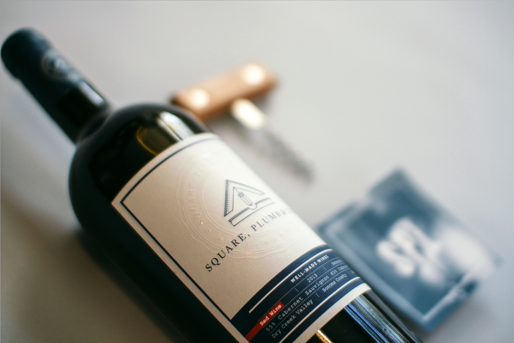 Detail of the square plumb and level wine label graphic design shows the logo icon and branding with an embossed seal and clear coat spot uv on the front label.