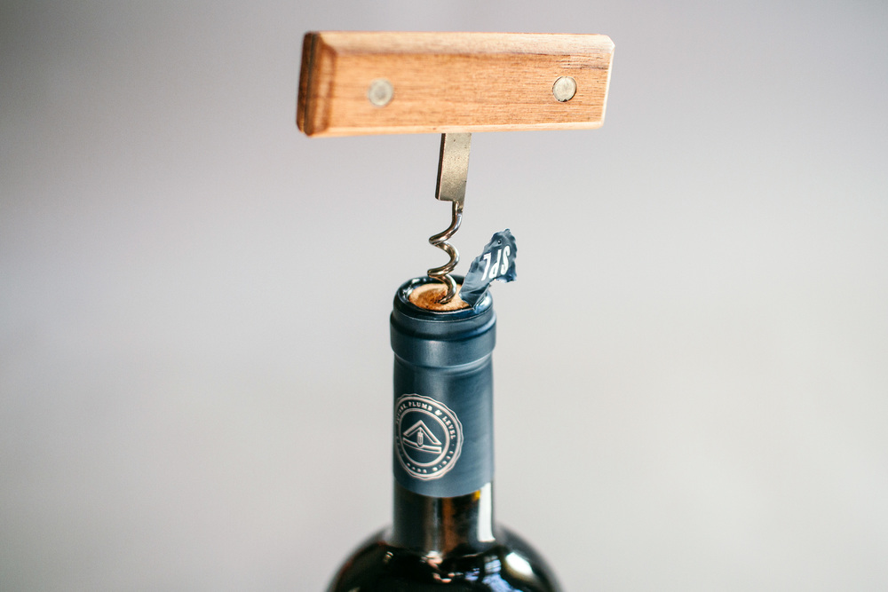 Uncorking the bottle of wine shows the Square Plumb and Level branding design on the top and side of the capsule.