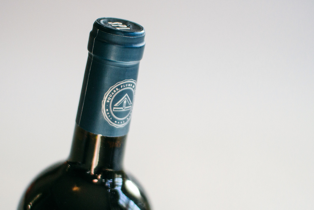 Wine capsule packaging and bottle design shows the Square Plumb and Level custom stamp letters on top and the icon seal on the side in silver on navy blue.