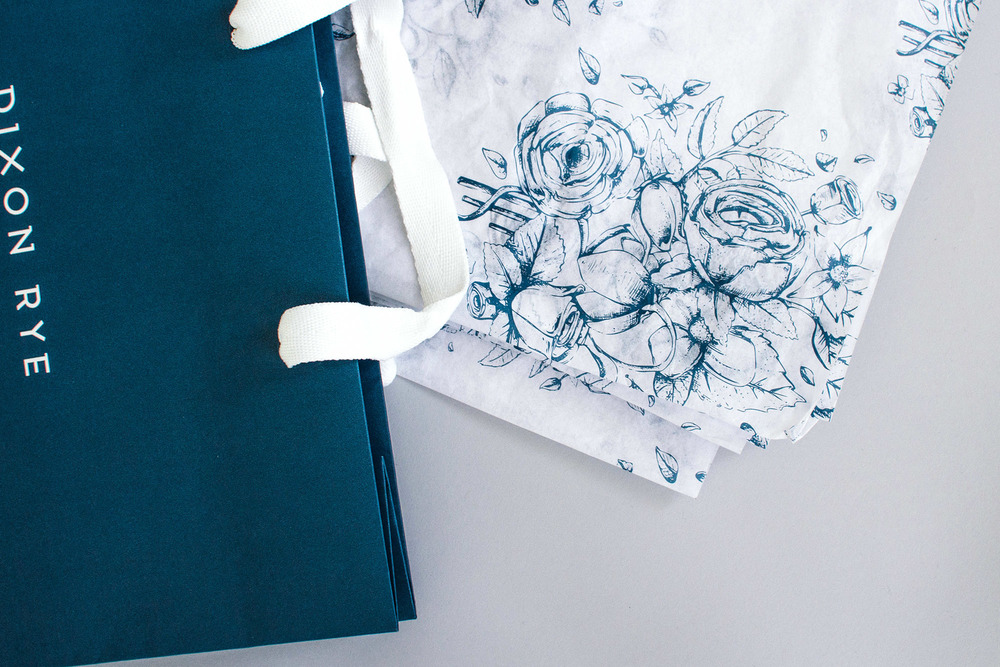 Detail of Dixon Rye's store packaging: a custom floral patterned tissue paper, hand drawn by illustrator Russell Shaw, next to the navy bag.