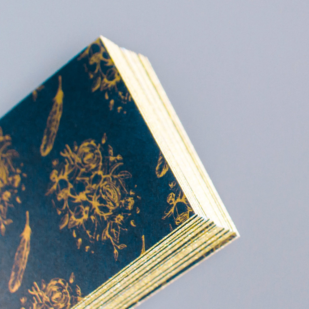 Detail of back of business card design, with the custom hand drawn floral and feather pattern, illustrated by Russell Shaw, printed in metallic gold on navy card for Dixon Rye's branding collateral.