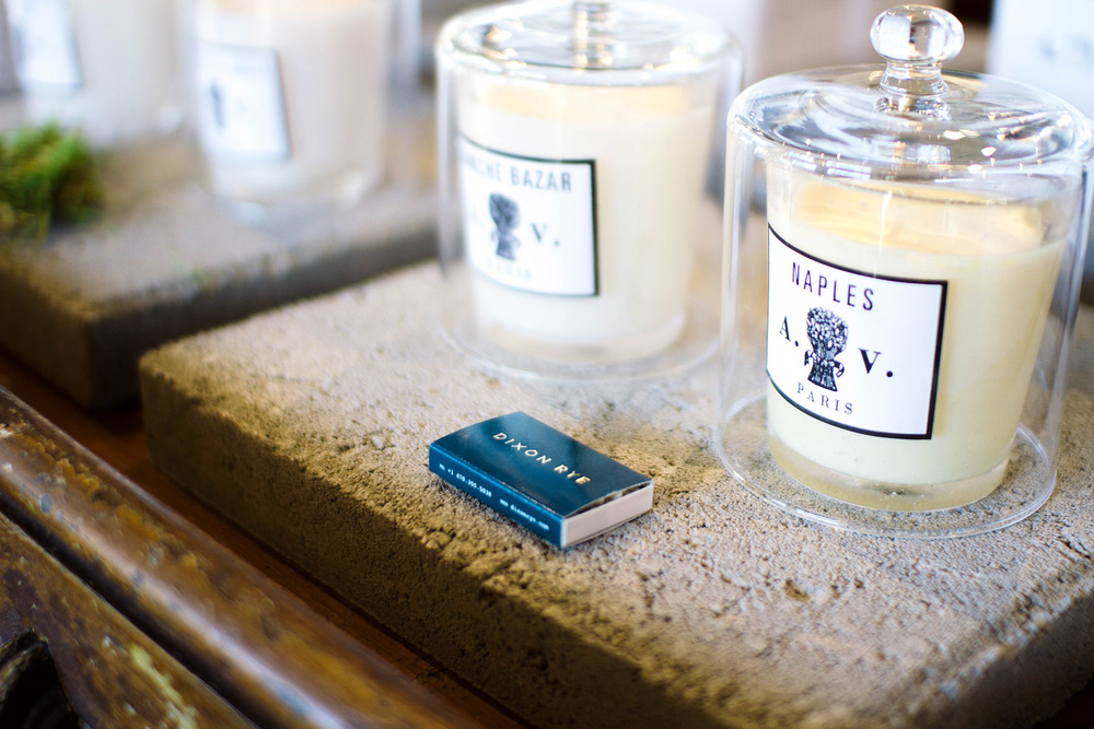Gold foil logo printed on a navy matchbox next to Astier de Villatte candles on stone table