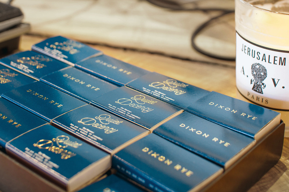 Box set of Quiet Decency and Dixon Rye custom gold foil on navy matchboxes next to Astier de Villatte candle.