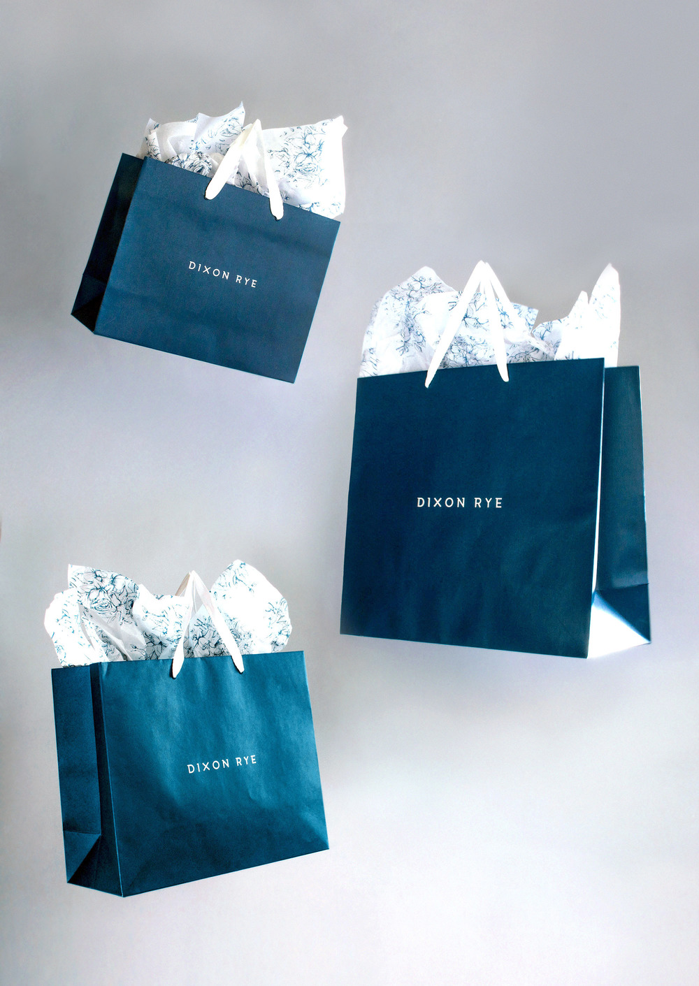 Dixon Rye's branded navy retail bags in three sizes, suspended in air.