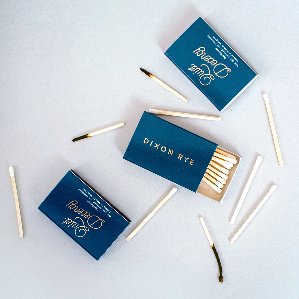 Custom white tip matches surround Dixon Rye's custom matchbox: a gold foil logo printed on a navy matchbox on the front, and Quiet Decency script lettering on the back.