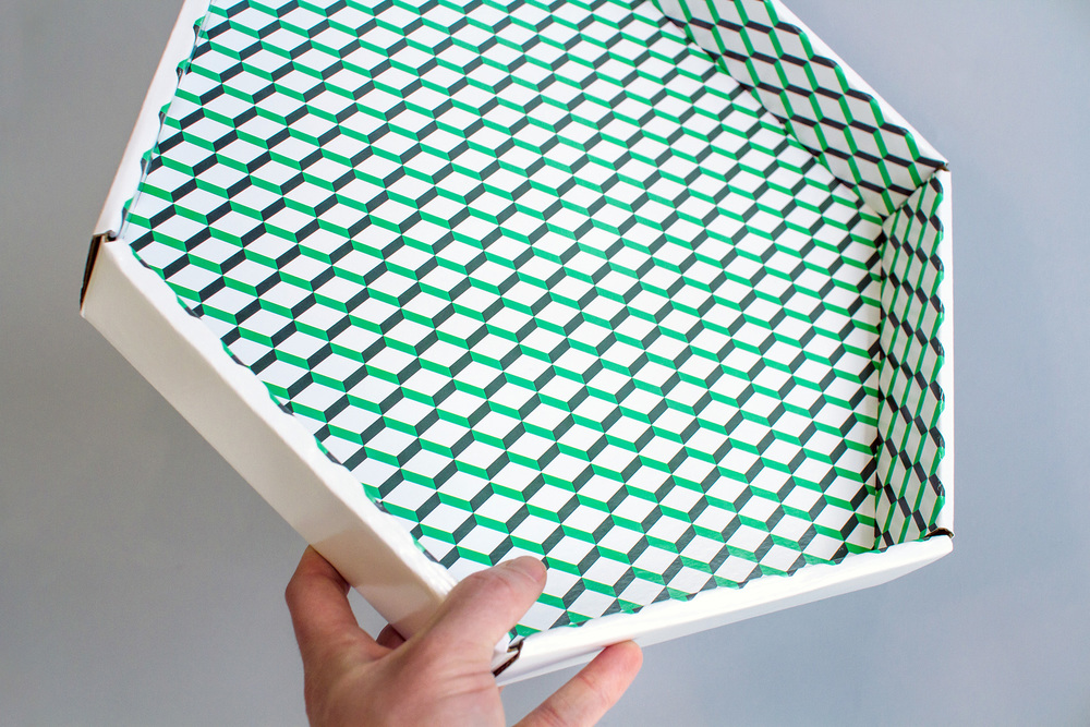 Inside the top lid of the hexagon packaging design is a graphic pattern made out of the logo that wallpapers the surface.