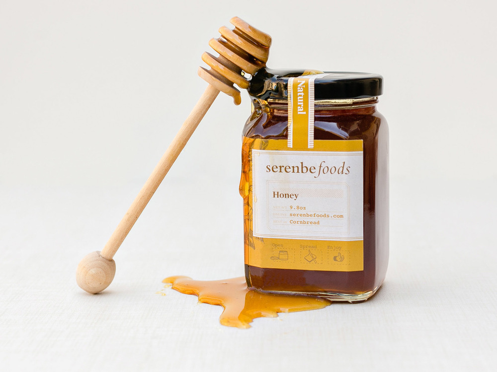 A honey comb leans against a spilled over jar of natural honey. Brand identity, graphic design, illustration and art direction for Serenbe Foods line of jams and consumer packaged goods.