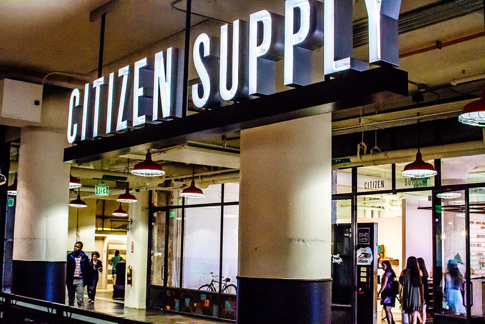 Citizen supply retail store sign with neon letters inside the custom logo design hanging above the store inside ponce city market atlanta.