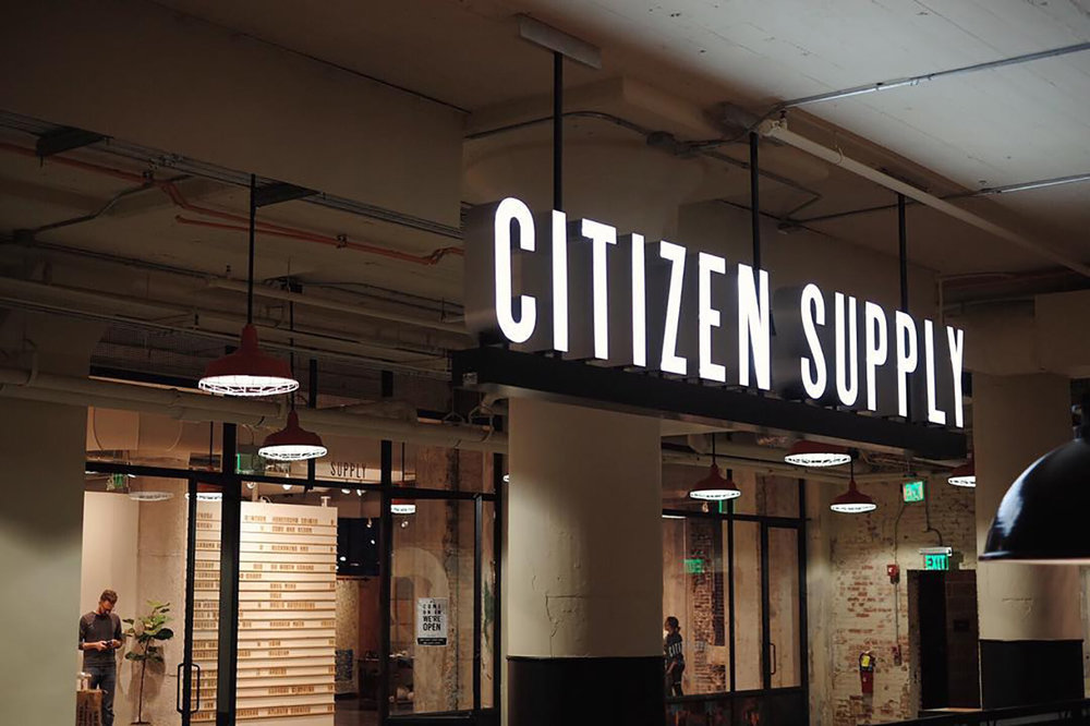 Environmental retail sign and branding for Citizen Supply neon and iron hanging sign in front of store inside Ponce City Market in Atlanta.