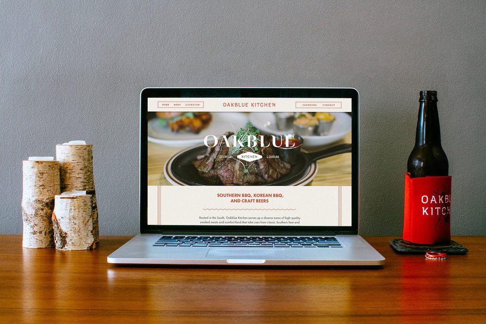 A laptop sits on a desk next to Oakblue Kitchen beer koozies, revealing the responsive homepage web site design for the restaurant, designed by Russell Shaw.