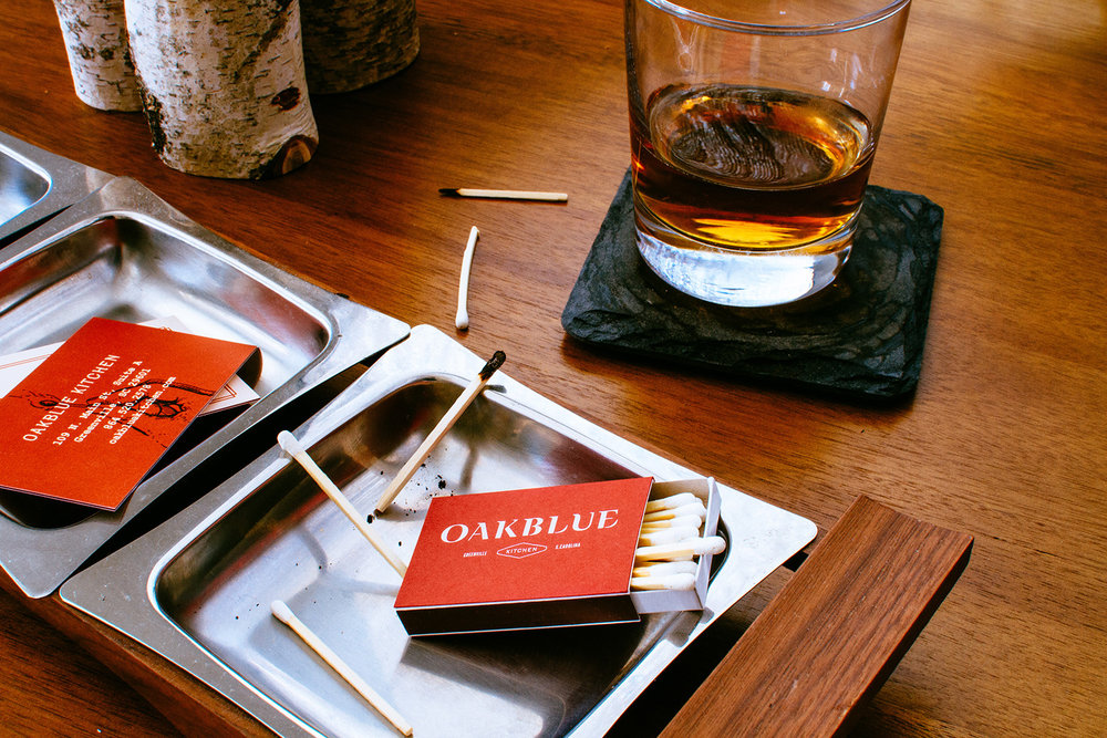 A red matchbox with white tip matches and the logo design for Oakblue Kitchen sits in a tray, next to the restaurant branded business cards and a glass of bourbon.