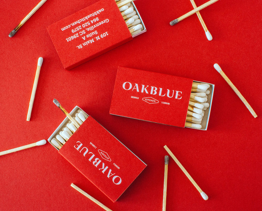 Oakblue Kitchen logo on red matchbox and matchbook, with matches around edges, for restaurant branding collateral.