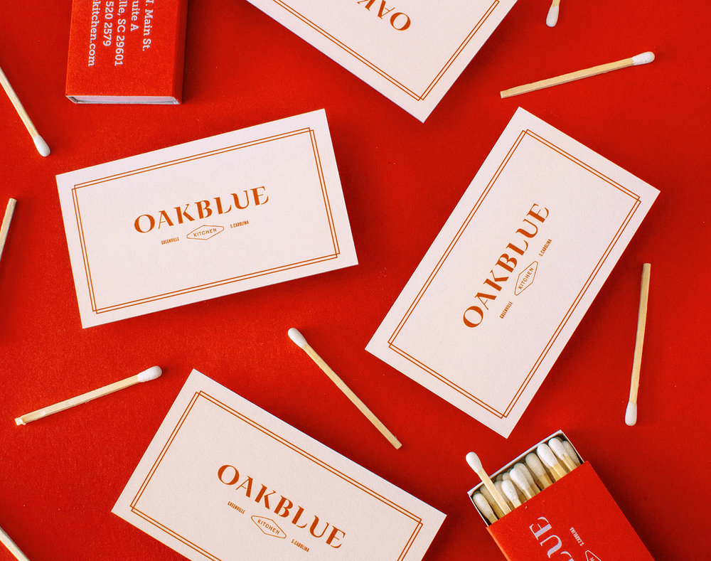Front of business card design for restaurant Oakblue, next to matches and custom designed matchbox strewn around.