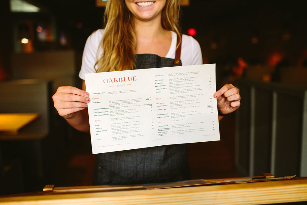 Restaurant photograph of woman holding the Oakblue Kitchen menu design.