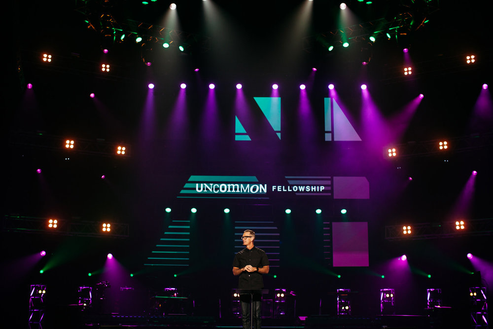Photograph of Mike Foster on stage at Catalyst Conference 2016 in Atlanta in front of screen design showing the visual branding identity for the Uncommon Fellowship event theme.