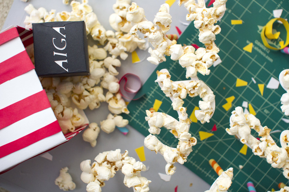 AIGA black logo made out of paper and a papercraft popcorn bag spilling real popcorn out on a cutting board with popcorn cursive script lettering and confetti all around, then photographed from above by artist Russell Shaw.