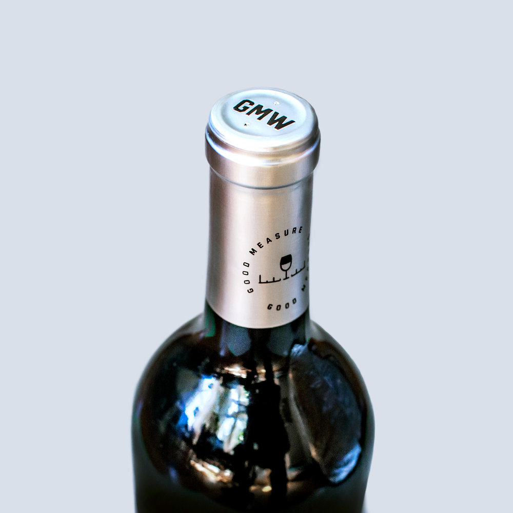 The top wine capsule design on the neck of the Good Measure Wines bottle has a GMW initials stamped on the top and the icon and logo design on the side of the silver wrapper.