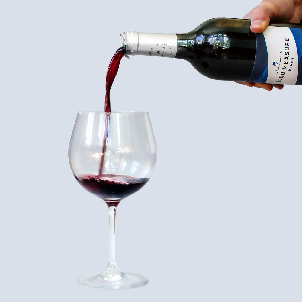 A bottle of Good Measure Wines cabernet sauvignon is tilted to pour the red wine into a glass.