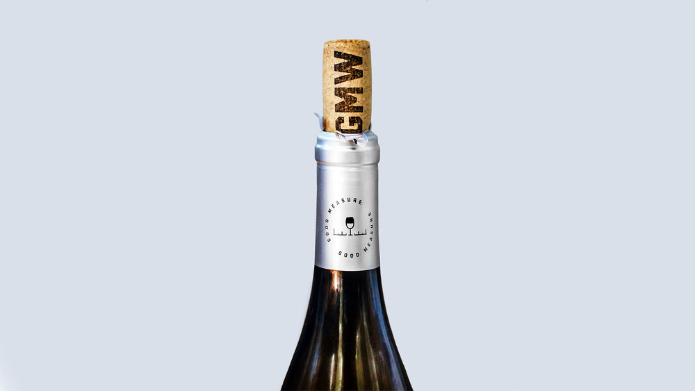 Good Measure Wines bottle neck capsule design and cork design shows the wine glass and ruler icon designed for the branding as well as the GMW initials stamped into the cork.