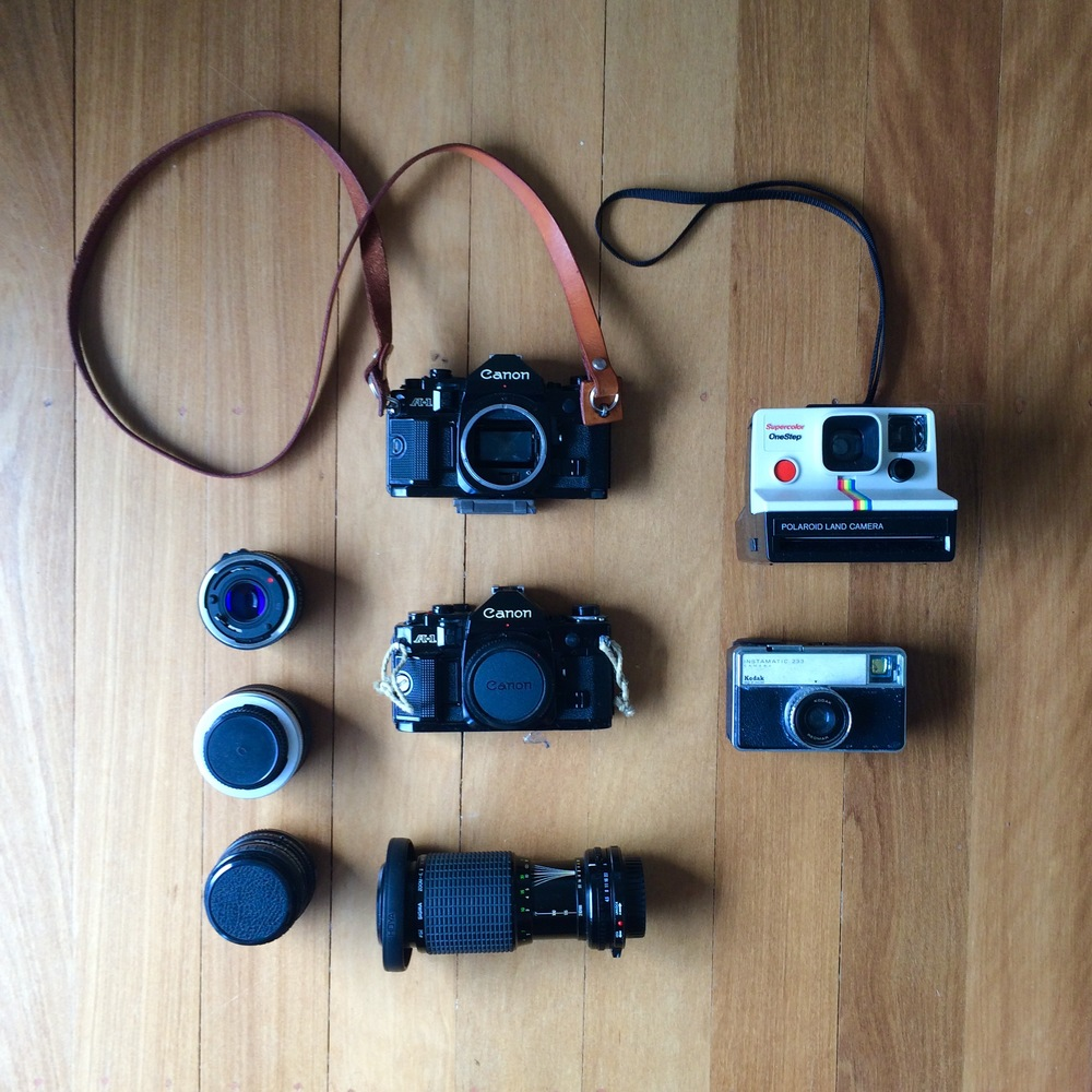 """Well I suppose you want the accessory kit?""  Camera: 2x Canon A1 bodies (including 1x handmade leather camera strap by  Chocolate Brownie Leather  (Aussie made) highly recommended), Polaroid OneStep Color, Kodak Instamatic 233  Lenses (Canon A1- FD mount: Top to bottom - Sigma 28mm f/1.8, Vivitar Macro adaptor, Canon 50mm f/1.8, Sigma 70-210mm f/4.5 - f/6.3 (probably)."