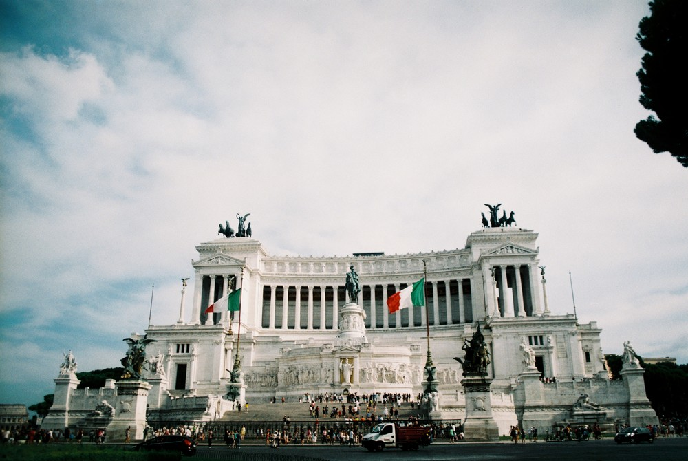 "The Altare della Patria ([alˈtaːre ˈdella ˈpaːtrja]; English: ""Altar of the Fatherland""), also known as the Monumento Nazionale a Vittorio Emanuele II (""National Monument to Victor Emmanuel II"") or Il Vittoriano, is a monument built in honour of Victor Emmanuel, the first king of a unified Italy, located in Rome, Italy. It occupies a site between the Piazza Venezia and the Capitoline Hill. (wikipedia)"