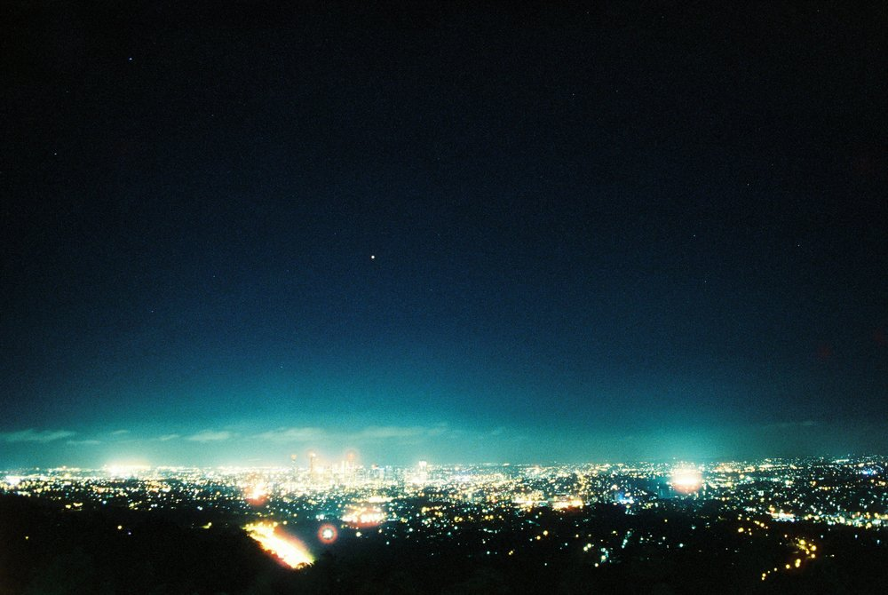 800T, view of Brisbane City by night from atop Mt Coo-tha. - Long exposure time, allowing for more light to hit the film and so because of this 'hotspots' occur with much brighter light sources. A sort of halation effect or cinematic effect. A little bit longer exposure time and stars would be much clearer.
