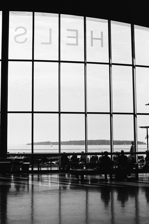 Helsinki Ship Terminal.  Framed with elements of the window pans. Both from the window and shiny floor. Elements of people using the space, waiting for their boat looking out into the harbour.