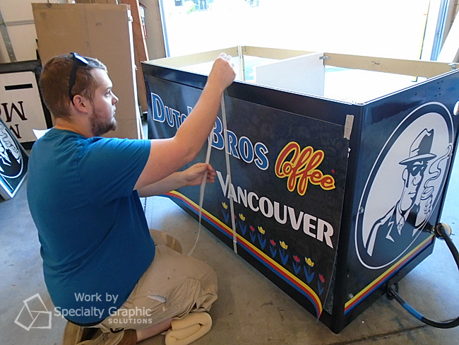Mighty Sign Makers wrapping a portable coffee cart for Dutch Bros in Vancouver WA.jpg