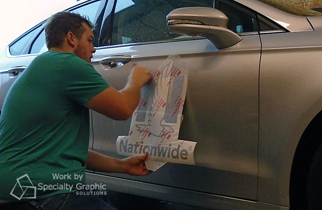 Mighty Sign Maker Taylor installing vehicle graphics at SGS Vancouver WA.jpg